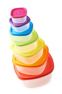 Pyramid pile of colorful rainbow colored plastic food containers, composition isolated over the white background