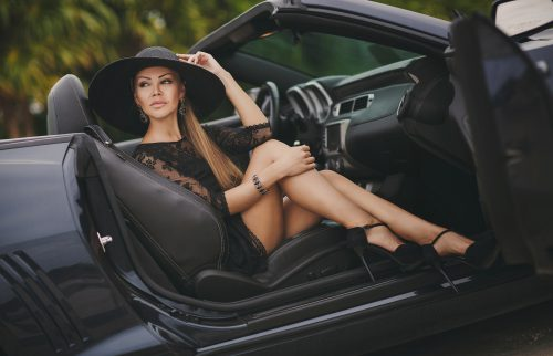 Portrait of a young lady in the car in a big black hat.